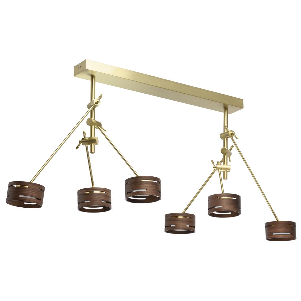 725010406 Чил-аут 6*5W LED 220 V люстра725010406Стильный светильник-трансформер - признанный тренд в мире светодизайна. Металлическое основание модели представлено в двух цветовых вариациях: матового золота и матового никеля. Главная изюминка светильника - оригинальные абажуры из натурального дерева, с графичными прорезями, красиво преломляющими световой поток. Абажуры также выполнены в двух оттенках: светлого и темного дерева. В качестве источников света выступают светодиоды, скрытые под вставкой из матового акрила, мягко рассеивающей свет. Помимо этого, светильник отличается богатым функционалом: его плафоны оснащены спот системой, а рожки трансформирующейся системой крепления. Это позволяет леко менять направление светового потока и самую композицию светильника.