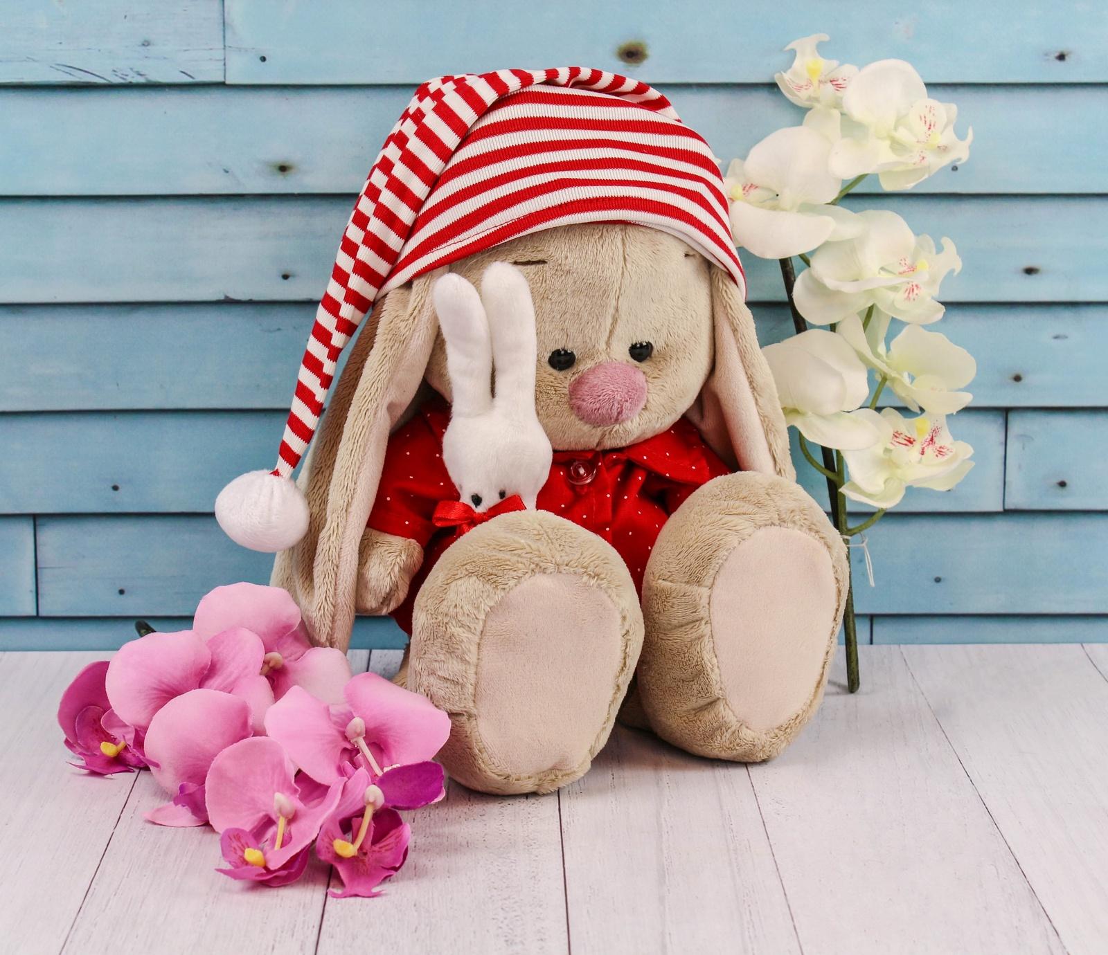 Мягкая игрушка BUDIBASA 23 см бежевый, красныйSidM-158/Зайки Ми - это милые зайчата Мия и Мика из волшебной страны мягких игрушек. Они обожают веселиться, пить ароматный чай на лужайке перед домиком, гулять по Плюшевому лесу и, конечно, стильно наряжаться. Ведь Мика занимается моделированием одежды и потрясающие наряды зайчат - именно его творения. А Мия, как настоящая девочка, обожает их примерять. Игрушка выполнена из невероятно мягкого материала, очень приятного на ощупь.