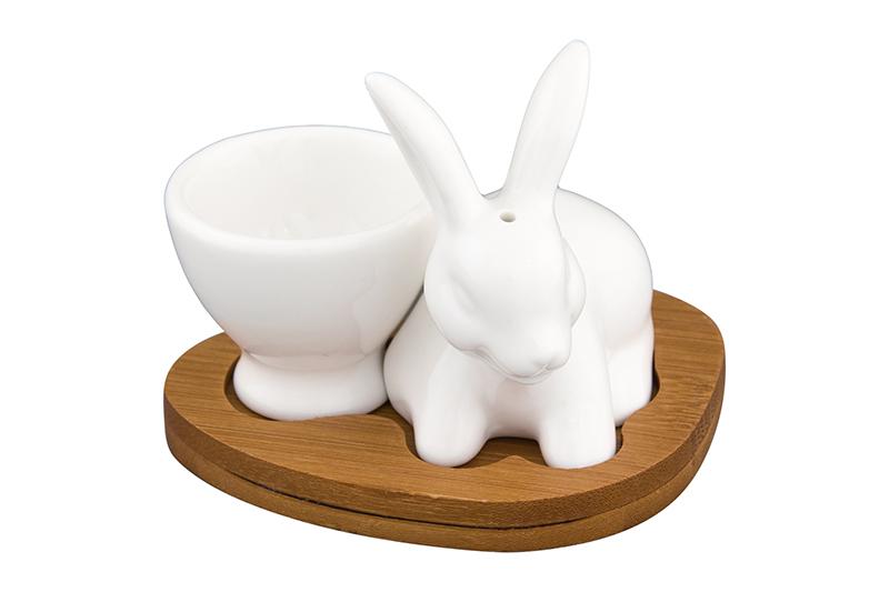 Подставка для яйца Elan Gallery Белый кролик, белый, коричневый540106Поставка под яйцо с солонкой в виде зайчика на деревянной подставке - прекрасный пример высококачественной, удобной и лаконичной посуды для изящной сервировки стола. Подставка под яйцо и солонка выполнены из прочного белого фарфора, а подставка из бамбука. Наполнить емкость для специй можно через отверстие в донышке, которое надежно закрывается пластиковой пробкой. В серии фарфоровой посуды с использованием бамбука представлен широкий ассортимент товаров для сервировки стола, которые несомненно впишутся в любой интерьер благодаря лаконичному дизайну, натуральным материалам и высокой функциональности. Такому подарку будет рада любая хозяйка!
