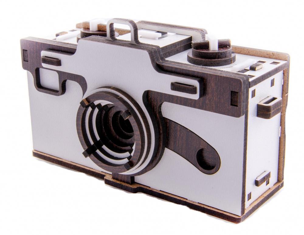 3D Пазл IQ Gears pinholepinhole3D пазл Pinhole Camera – уникальный деревянный 3D конструктор фотоаппарат, который позволяет делать снимки через маленькое отверстие, используемое вместо объектива. Выполнен из экологически чистых пород дерева, все детали собираются без клея. Развивает навыки по физике и механики, мелкую моторику рук, нацеленность к результату и пространственное видения модели. Спецификация конструктора: Время для сборки – 60 минут, может отличаться, размеры собранного фотоаппарата – 136*85*59 мм, пинхол диаметр – 0,2 мм, фокусное расстояние – 24 мм. Комплектация: Набор деталей, фольга, игла, наждачная бумага, инструкция по сборке, брошюра с примерами фотографий, запасные детали.